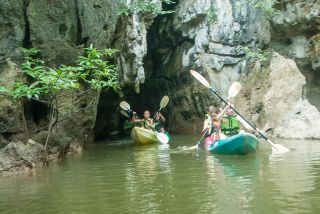 Paddling out of one of the caves carved by nature right through the mountains